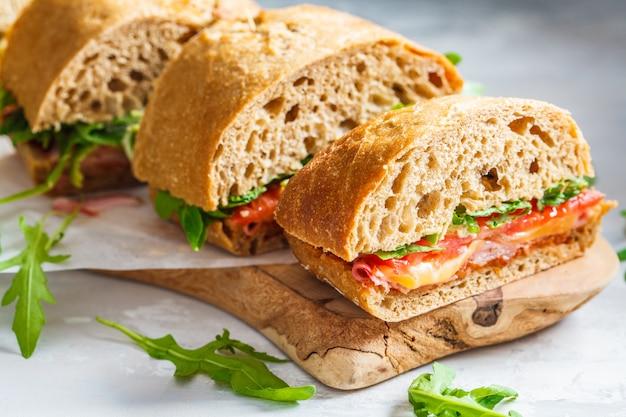 Sanduíches com ciabatta, presunto e legumes em uma placa de madeira Foto Premium