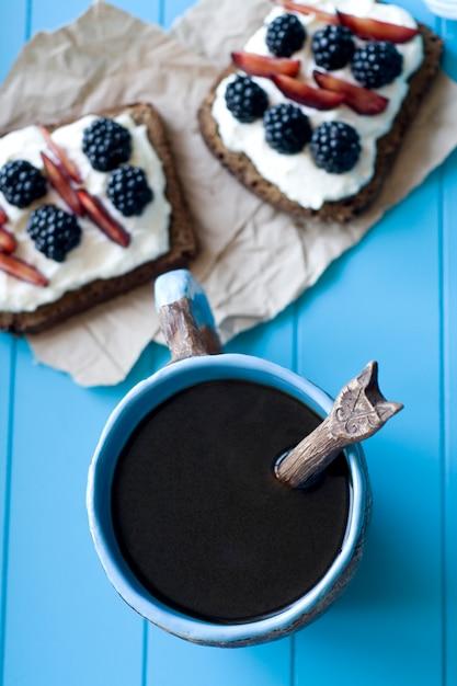 Sanduíches com queijo doce e frutas, uma xícara de café na superfície de madeira azul Foto Premium