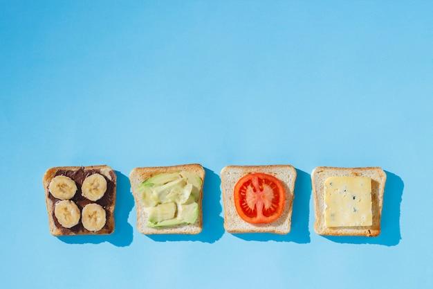 Sanduíches com queijo, tomate, banana e abacate numa superfície azul. conceito de alimentação saudável, café da manhã no hotel, dieta. iluminação natural, luz dura. vista plana leiga, superior. Foto Premium