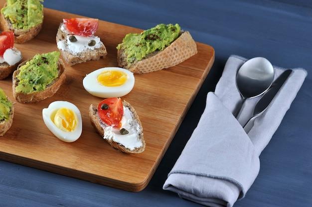 Sanduíches de canapé em uma placa de madeira Foto Premium