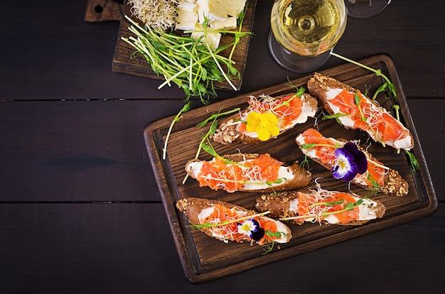 Sanduíches de salmão com cream cheese e microgreen na mesa de madeira Foto Premium