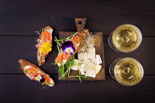 Sanduíches de salmão com creme de queijo e microgreen na mesa de madeira. Foto Premium