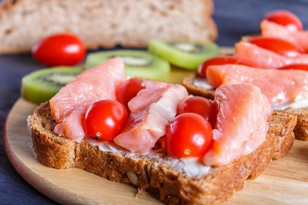 Sanduíches de salmão defumado com manteiga e tomate cereja em fundo preto de madeira Foto Premium
