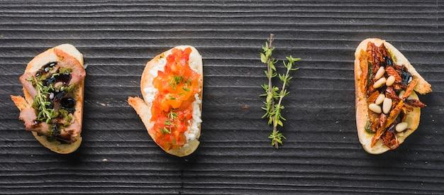 Sanduíches de torrada caseira com tomilho sobre fundo preto de madeira Foto gratuita