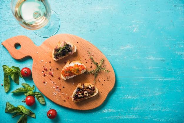 Sanduíches de torrada com tomilho; manjericão e tomate e vinho no cenário pintado Foto gratuita