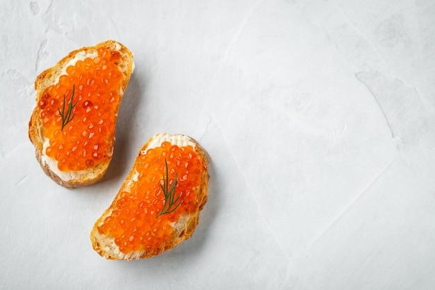 Sanduíches deliciosos com caviar vermelho. fundo com copyspace Foto Premium