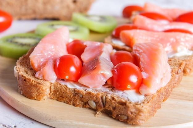 Sanduíches do salmão fumado com manteiga e tomates de cereja no fundo de madeira branco. Foto Premium