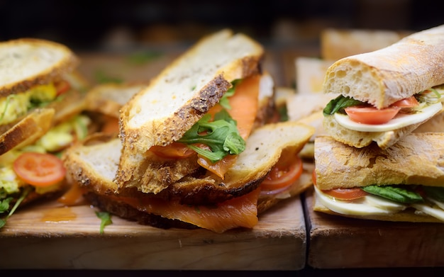 Sanduíches frescos na tábua de madeira nas vitrines do café ou restaurante Foto Premium