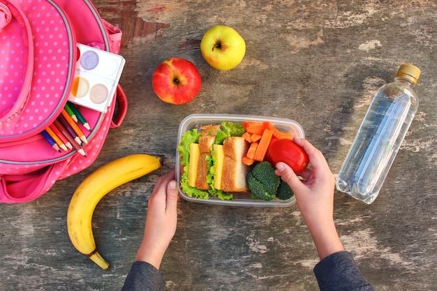 Sanduíches, frutas e legumes na caixa de comida Foto Premium