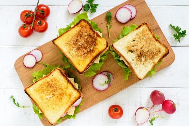 Sanduíches multicamadas com uma costeleta suculenta, queijo, rabanete, pepino, alface, rúcula em uma tábua vista superior. Foto Premium