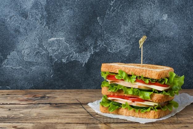 Sanduíches saborosos e frescos em uma mesa de madeira escura. Foto Premium
