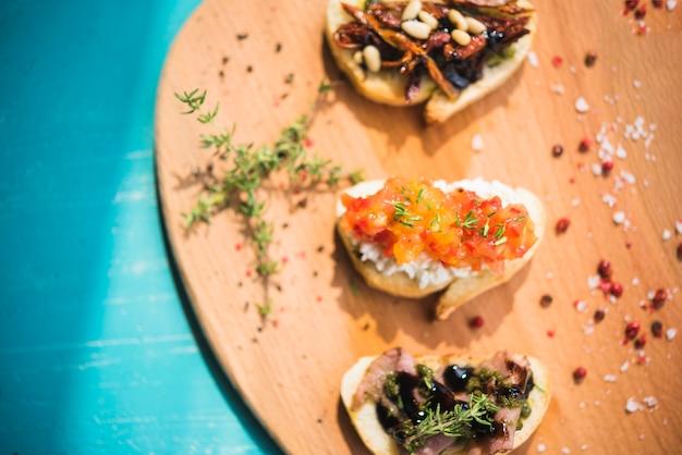Sanduíches tostados com tomilho; pimenta e sal na placa de madeira Foto gratuita