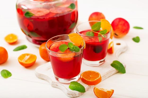 Sangria com frutas e hortelã em um branco Foto gratuita