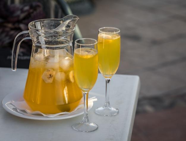 Sangria de champanhe amarela servida em uma caneca com dois copos Foto Premium