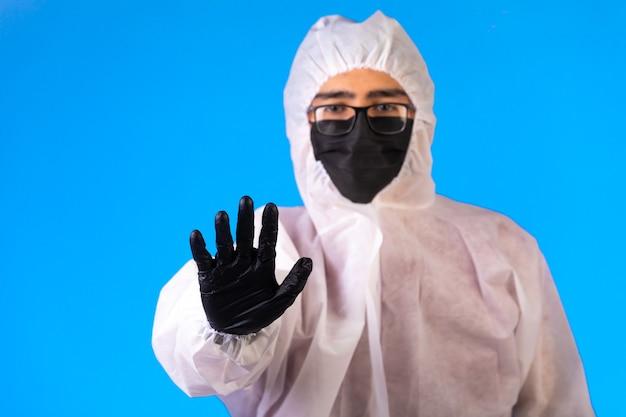 Sanitizante em uniforme preventivo especial e máscaras na cor azul Foto gratuita