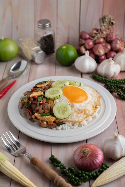 Santo manjericão arroz frito com coração de frango e ovo frito sobre um piso de madeira branco. Foto gratuita