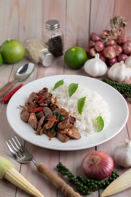 Santo manjericão arroz frito com coração de frango em um piso de madeira branco. Foto gratuita