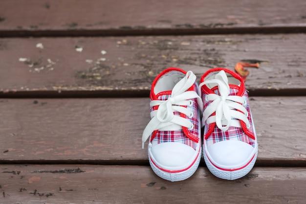 Sapatas de bebê vermelho e branco na cadeira de madeira Foto Premium