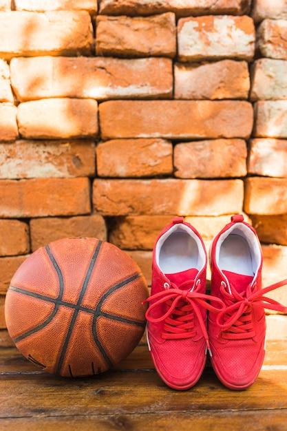 Sapatas do esporte vermelho e basquete contra a pilha de parede de tijolo Foto gratuita