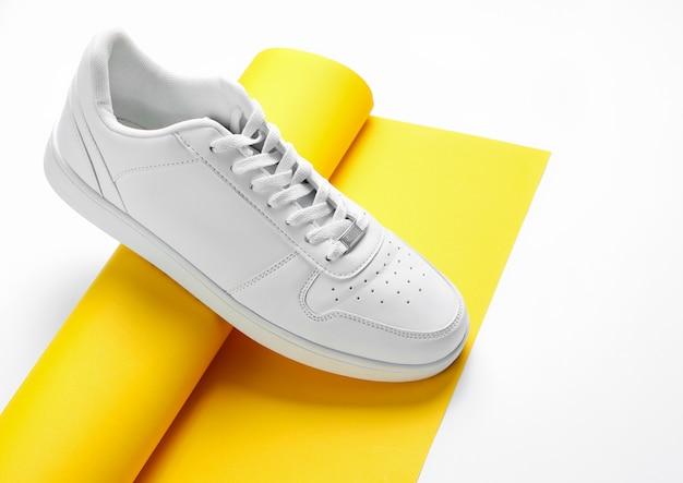 Sapatilha branca em rolo enrolado de papel amarelo. Foto Premium