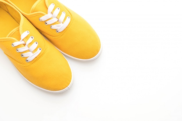 Sapatilhas amarelas sobre fundo branco Foto Premium