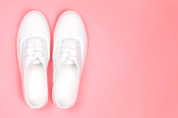 Sapatilhas brancas em um close-up cor-de-rosa do fundo, cópia spacefashion tendência das sapatas. Foto Premium