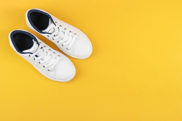 Sapatos brancos, tênis com cadarço amarelo Foto Premium