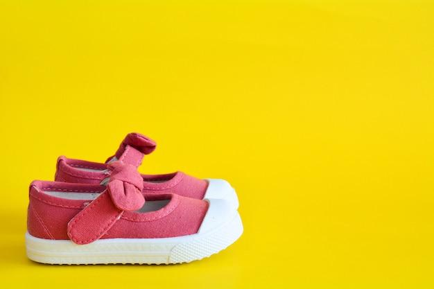 Sapatos cor de rosa para crianças em amarelo. Foto Premium