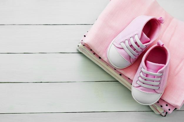 Sapatos de bebê rosa menina e roupas recém-nascidas. conceito de maternidade, educação ou gravidez com espaço de cópia. configuração plana. Foto Premium