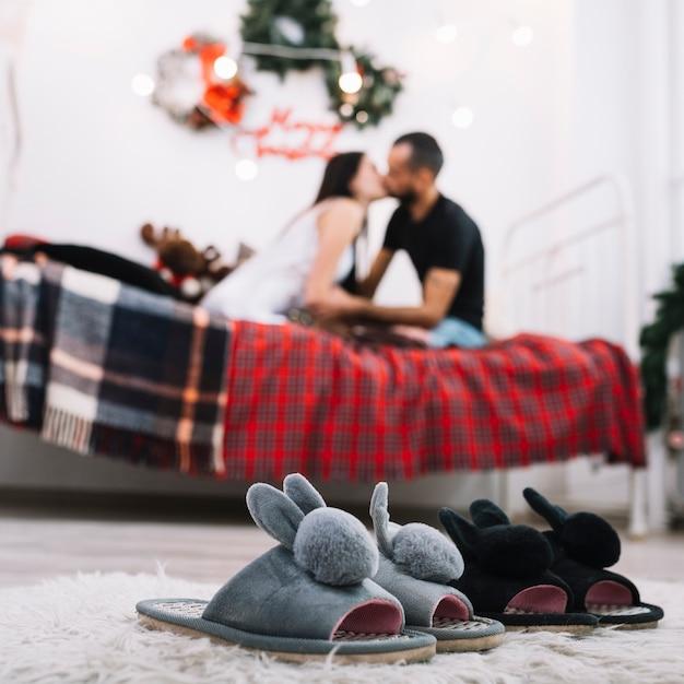 Sapatos de casa aconchegante no chão perto beijando casal na cama Foto gratuita