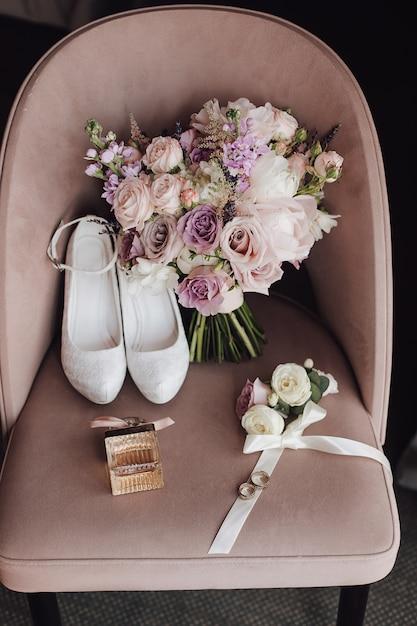 Sapatos de casamento, buquê de flores cor de rosa e roxas na cadeira Foto gratuita