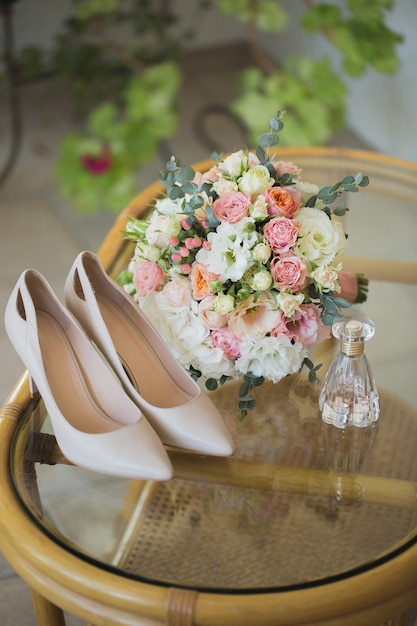 Sapatos de casamento com buquê de flores e perfume Foto Premium