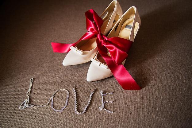Sapatos de casamento de jóias amarrados com um laço vermelho Foto Premium