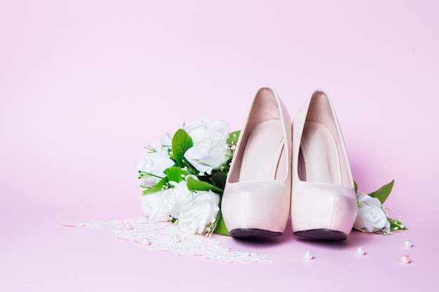 Sapatos de casamento e buquê deitado no rosa. fechar-se Foto Premium