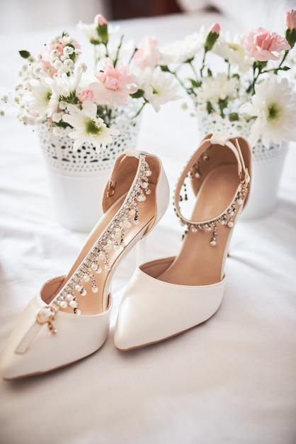 Sapatos de casamento nupcial branco elegante, perfume, flores e jóias. Foto Premium