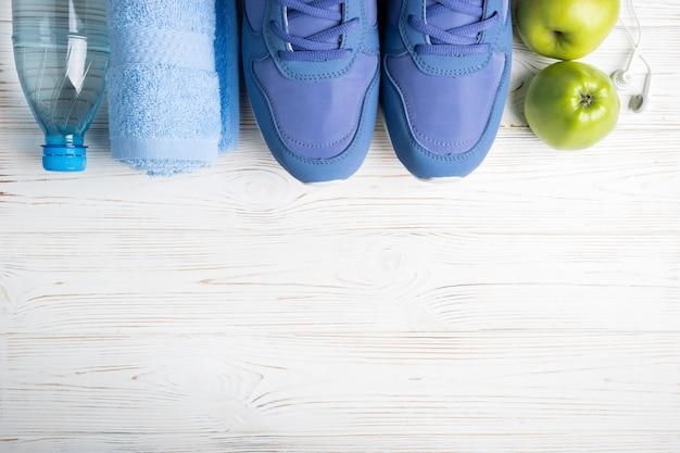 Sapatos de desporto plana leigos, garrafa de água, maçãs, toalha e fones de ouvido em branco. Foto Premium