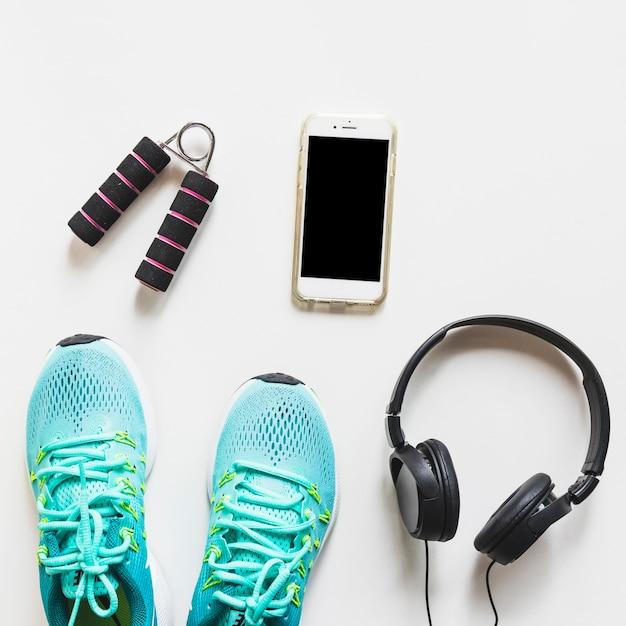 Sapatos de desporto turquesa; fone de ouvido; celular e aperto de mão sobre fundo branco Foto gratuita