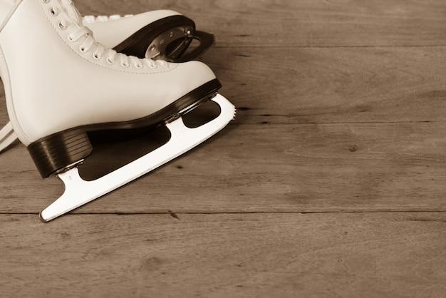 Sapatos de patinação no gelo figura estilo feminino ou mulheres em fundo de madeira Foto Premium