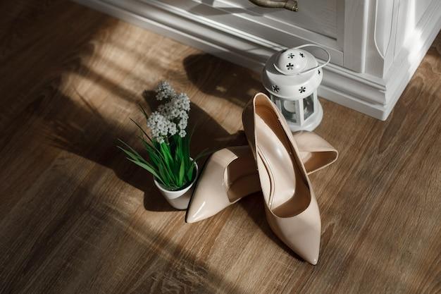 Sapatos de salto alto bege isolados no fundo de madeira com espaço de cópia de texto Foto Premium