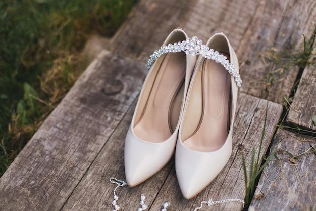 Sapatos de salto alto bege, sapatos e jóias de casamento estão sobre uma mesa de madeira vintage Foto Premium