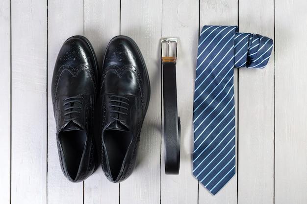 Sapatos e acessórios para homens colocam no chão de madeira Foto Premium
