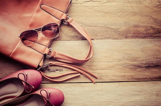 Sapatos e bolsas de couro para mulher colocada sobre um piso de madeira. Foto Premium