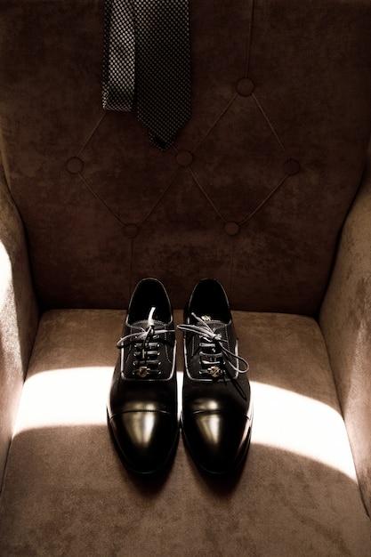 Sapatos elegantes do noivo encontram-se numa poltrona macia Foto gratuita