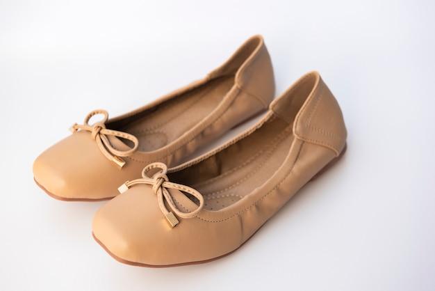 Sapatos femininos de cor creme, colocados em uma parede branca Foto Premium