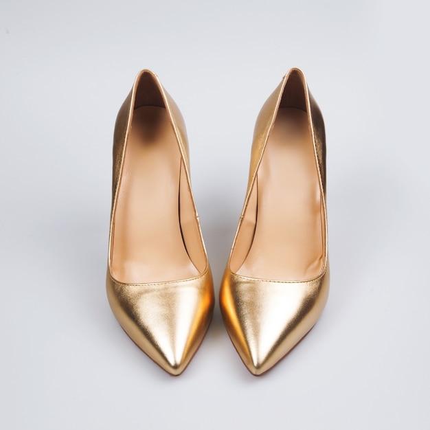 Sapatos femininos de ouro sobre branco Foto Premium