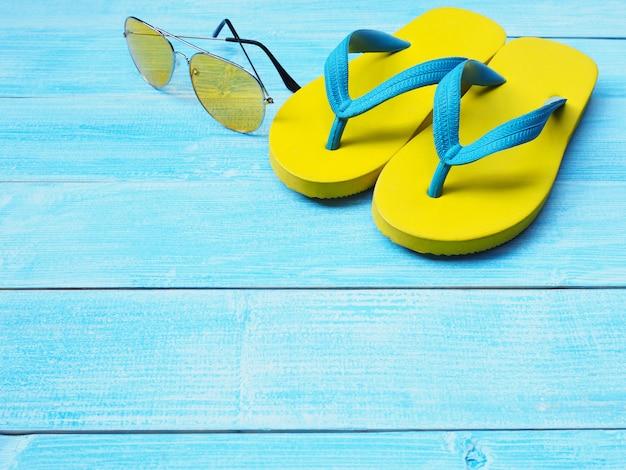 Sapatos flip flop amarelo e óculos escuros sobre fundo azul de madeira Foto Premium