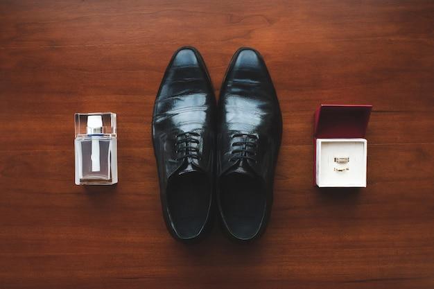 Sapatos pretos, anéis de noivado e perfume masculino no chão. acessórios para o noivo no dia do casamento. Foto Premium