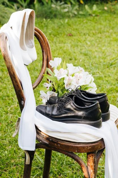 Sapatos pretos de casamento e saltos altos brancos com buquê de flores na cadeira de madeira no jardim Foto gratuita