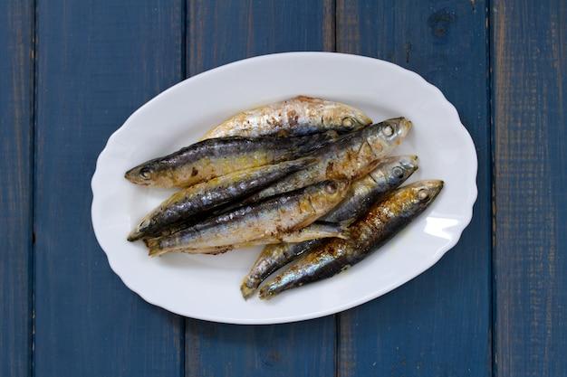 Sardinhas fritas no prato branco na superfície de madeira azul Foto Premium