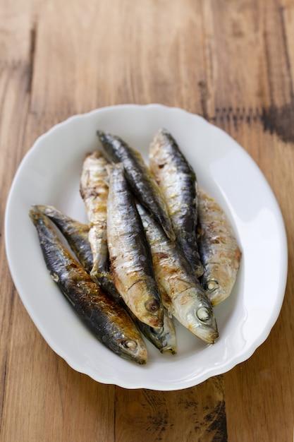 Sardinhas fritas no prato branco na superfície de madeira marrom Foto Premium